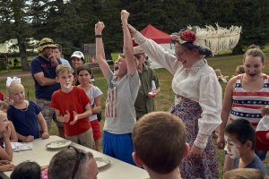 Lady historic interpreter holding up arm of young man celebrating his victory of pie eating contest with spectators all around.