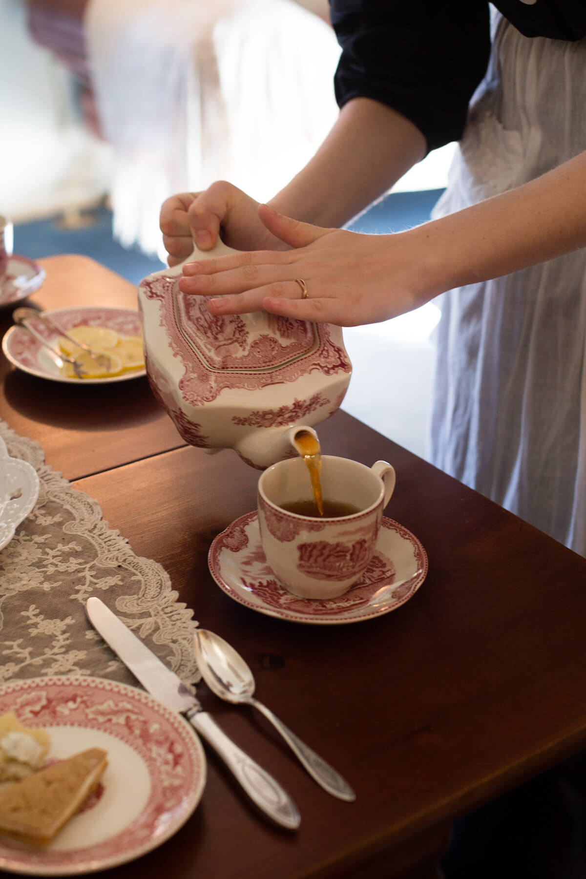 Domestic servant pouring tea into china cup.