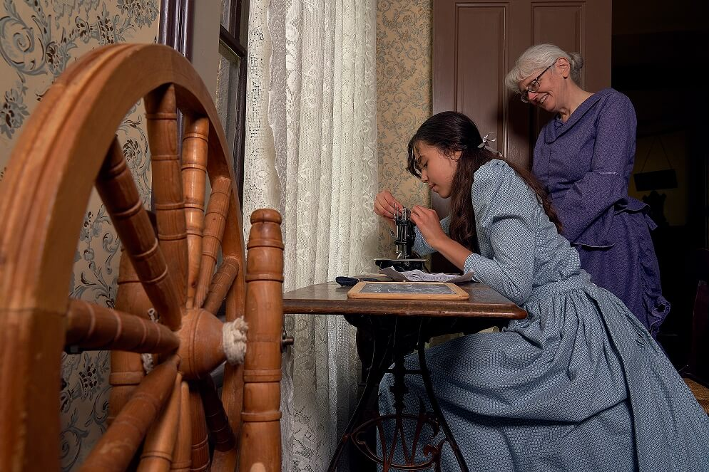 Spinning wheel. Historic interpreters using the antique sewing machine