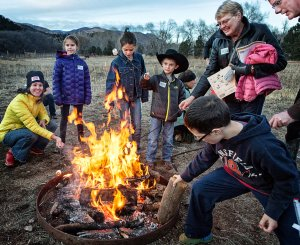 Families and visitors around a campfire roasting marshmallows.