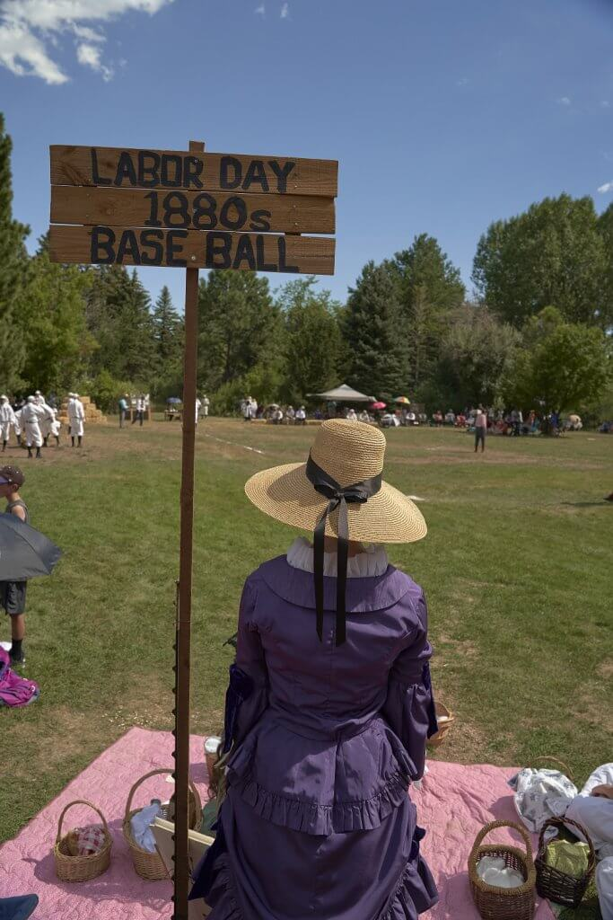 Lady in 1800s dress sitting by Labor Day 1880s Base Ball sign, viewing game.
