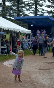 Girl with umbrella at bluegrass event with spectators and stage with musicians in the background